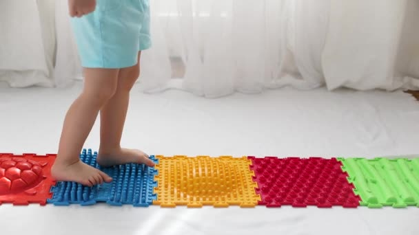 Kid boy walks on orthopedic colored rugs for the treatment of valgus feet x legs, close-up on a white background. Childrens diseases of the musculoskeletal system.
