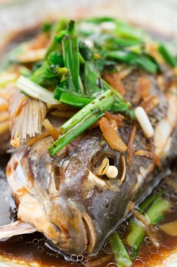 fresh steamed whole fish covered with herbs onions and sauce close up