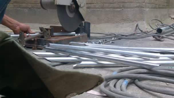 dělník, řezání ocelových trubek s kotoučovou pilou