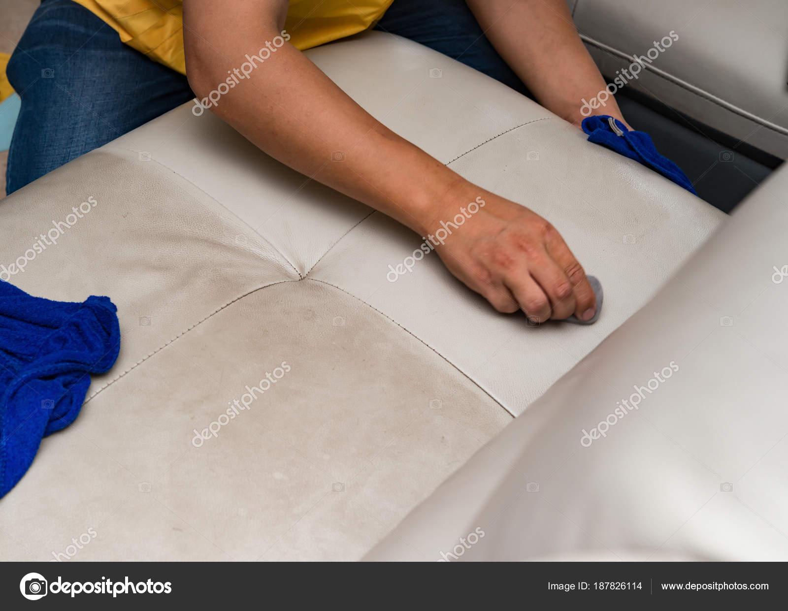 Pulizia divano pelle casa con spugna asciugamano u foto stock
