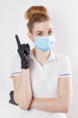 Egy lány orvosi maszkban és gumikesztyűben. Védőeszközök a karanténban. Maszk és kesztyű.