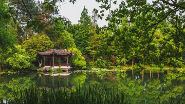 Traditional Chinese architecture by water in park by West Lake,