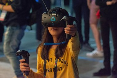 A woman plays a video game using virtual reality glasses