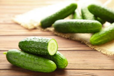 Fresh cucumber slices on brown wooden background. Top view