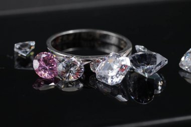 Macro shoots of a group of gold wedding ring and diamonds that has different shapes, heart, round, pear, asscher, oval, princess, isolated background