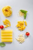 Raw pasta set  and tomato on light background