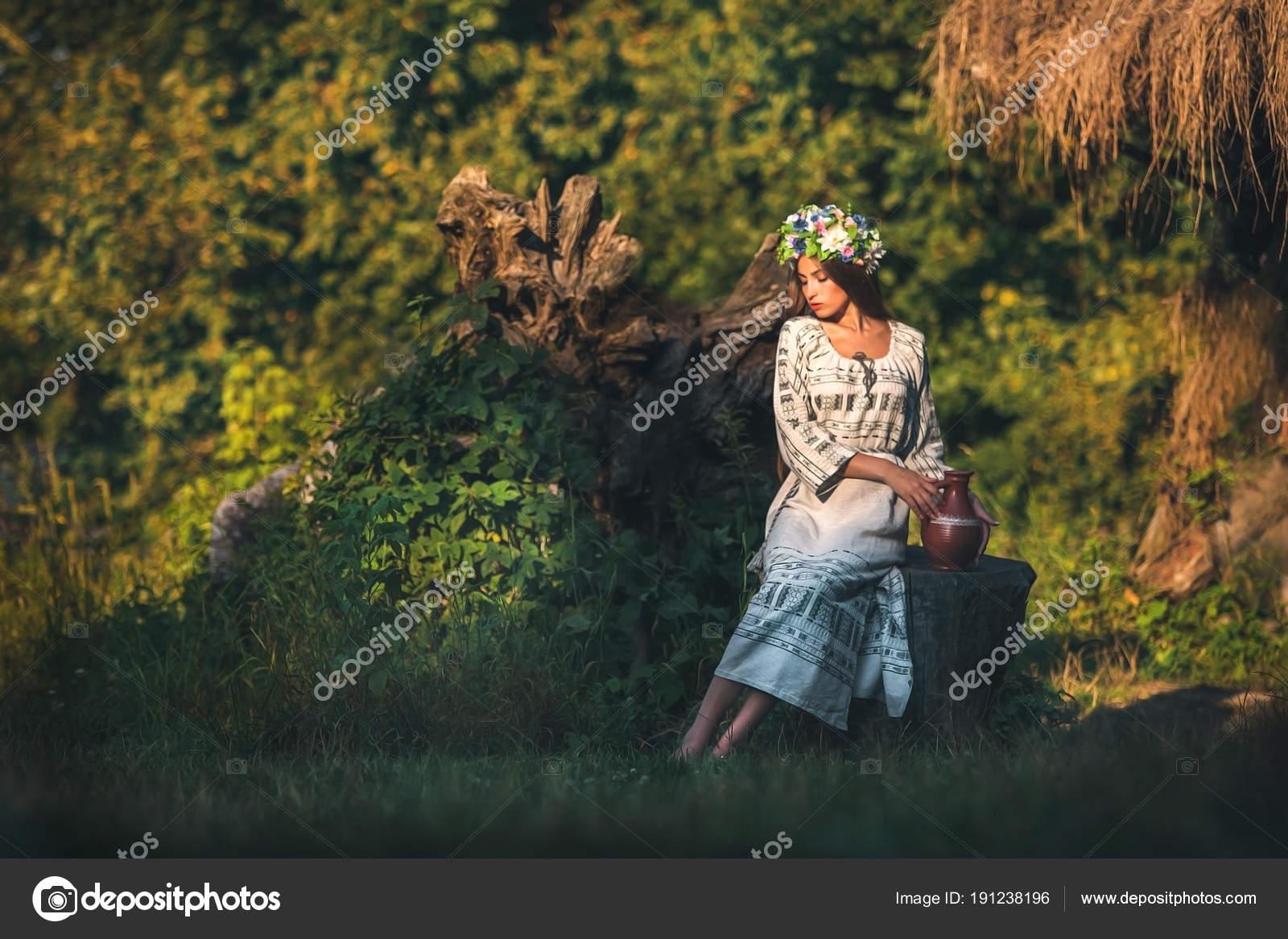 20fb49bf07 Siedzi brunetka w Wyszywana sukienka lniana z wzorami na pniu z dzbanem —  Zdjęcie od style-photo. Znajdź podobne obrazy