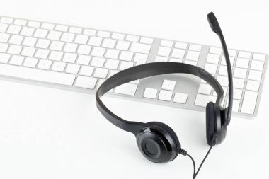 Computer headset with microphone on computer keyboard on white t