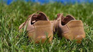 Sports gym shoes on a green grass
