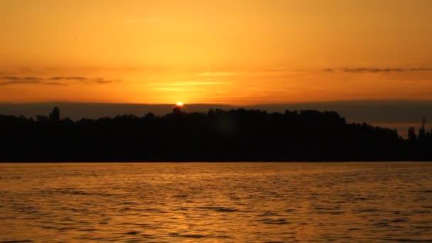 Krásný západ slunce, západ slunce mizí za obzorem s ostrovem. Romantická scéna u moře večer.