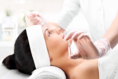 Cosmetic ampoule, a woman in the beauty salon, vitamin C in cosmetic ampoule.