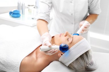 Relaxing facial massage. Massage the face with glass balls.