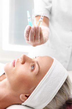 Vitamin cocktail in an ampoule, a woman in the beauty salon.Cosmetic ampoule, serum applied to the face of a woman.