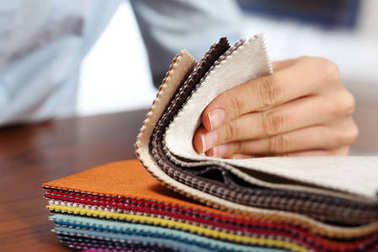Sampler of fabric colors.The woman watches the colors and patterns of upholstery fabrics.