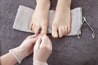 Pedicure, Foot care, female feet during a pedicure at a beauty salon. The beautician performs a pedicure treatment. Bare feet on a gray towel during care treatment. Natural photo no retouching.