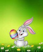 Karikatura malý zajíček drží velikonoční vajíčko