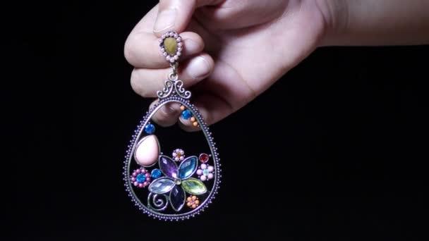 Žena ukazuje drahokam zdobené šperky náušnice v prstech.
