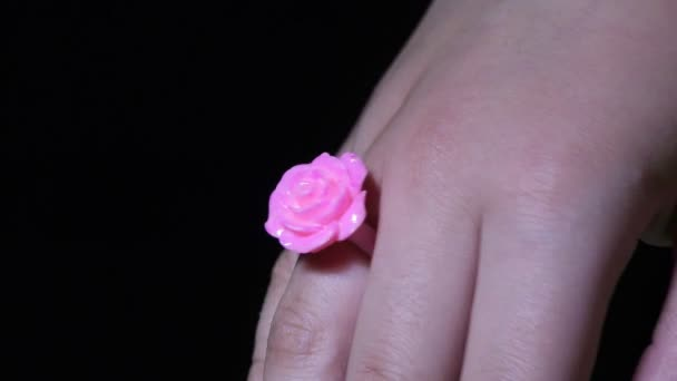 A woman wearing pink rose ring in the finger and showing, ring finger