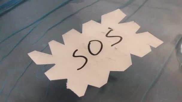 SOS zpráva na papíře plovoucí na vodě a vlny.