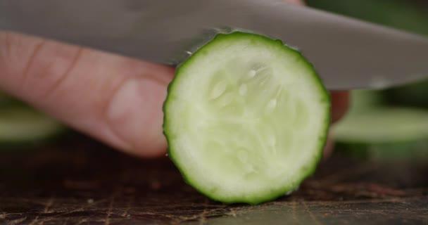 Slicing fresh cucumber close -up.