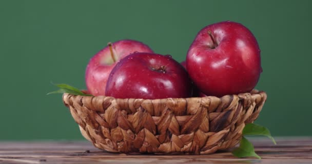 Rotating fresh red apples in basket .