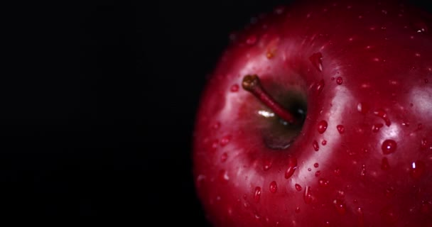 Rotating fresh red apples with water drops.