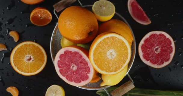 Colander with slices of different citrus slowly rotates.