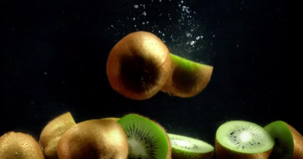 Half of kiwi falling under the water with air bubbles.