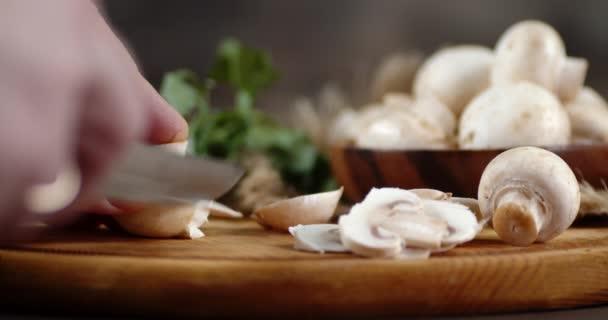 Hände Männer schneiden den Pilz in Stücke.