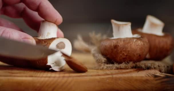 Mužské ruce krájení čerstvé houby na dřevěné desce.
