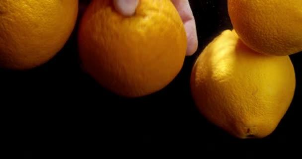 Mužská ruka s čerstvými pomeranči pod vodou.
