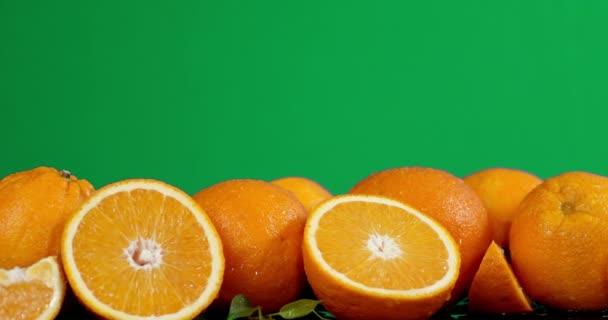 Whole and sliced fresh oranges slowly rotate.