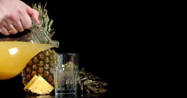 Mužská ruka nalévá šťávu ze zralého ananasu do sklenice.