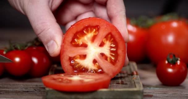 Ruka muže s nožem rozseká čerstvé rajče na kousky.