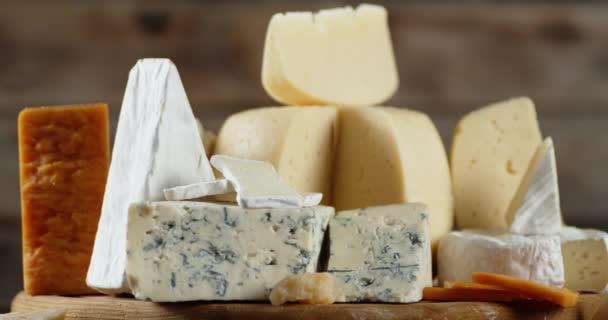 Různé odrůdy sýra na řezném prkně pomalu rotují.