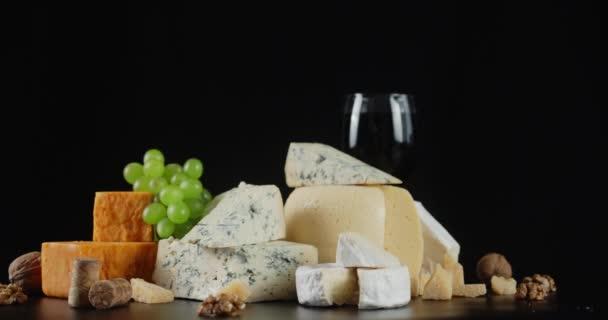 Různé druhy sýrů na stole se pomalu otáčí.