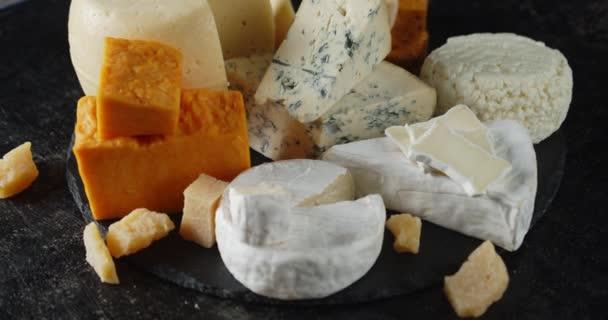 Různé druhy sýrů na kamenné desce se pomalu otáčejí.
