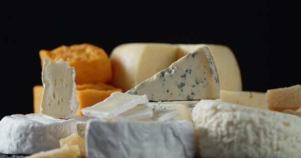 Kousky různých sýrů se pomalu otáčejí.