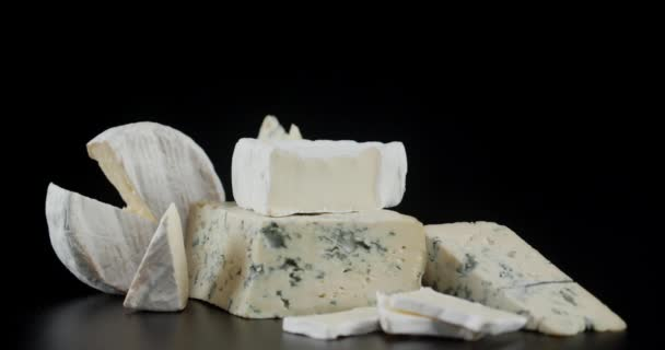 Řada různých druhů sýrů se pomalu otáčí.