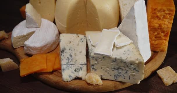 Kusy různých sýrů na řezací desce se pomalu otáčí.