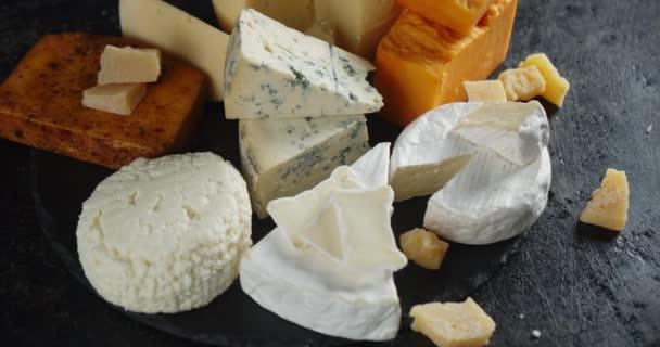 Kousky různých druhů sýra na kamenné desce.