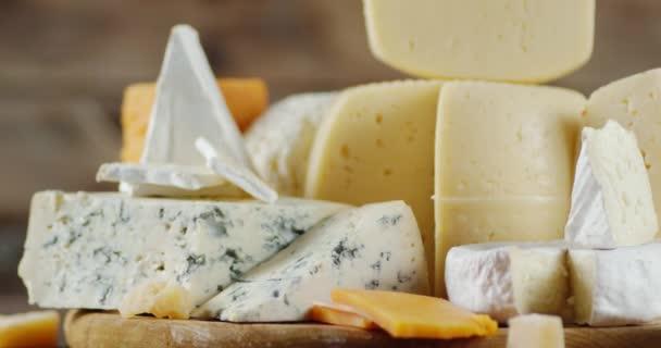 Řada sýrů na řezací desce se pomalu otáčí.