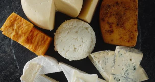 Sada různých sýrů se pomalu otáčí.