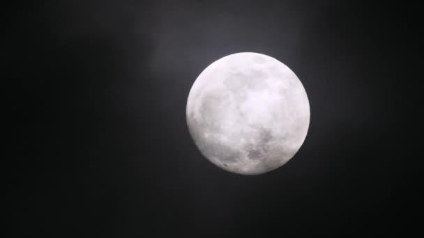 Úplněk za temné oblačné noci. Mraky míjejí měsíc, záběr v reálném čase.
