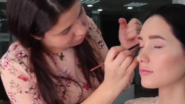 Make-up-Artist schminkt die Augen des Models, legt Schatten auf das Augenlid, in einem professionellen Studio. Konzept professioneller Lidschminke, Make-up, Videotechniken zum Auftragen von Lidschatten.