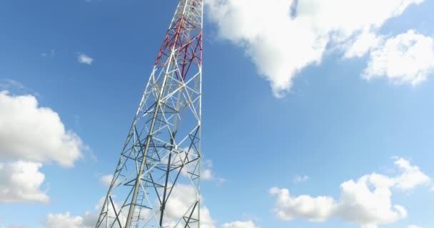 Video komunikační věže zdola s bílými mraky v pozadí.