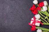 červené a bílé tulipány a zabalená krabice s prezentovat na černém texturou pozadí