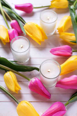 Bright pink and yellow tulips  flowers and candles  on white wooden background. Selective focus. Top view.