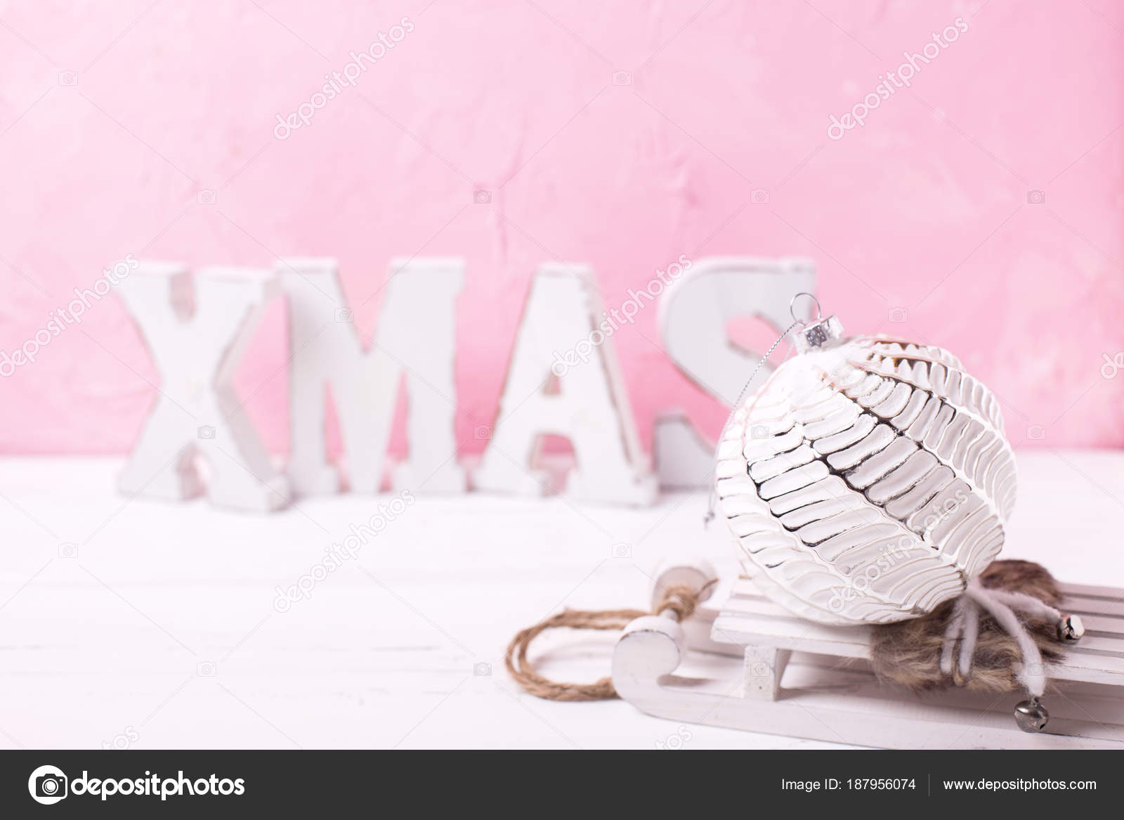 white ball and word xmas made from wooden letters on white wooden background against pink wall place for text photo by daffodil