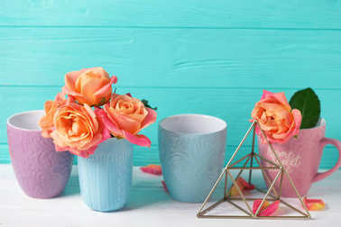 Fesh orange roses and colorful cups  against  turquoise wall. Place for text. Floral still life. Selective focus.